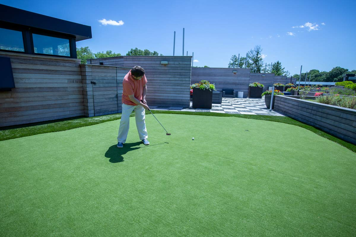 Man playing golf on the JLOFTS Rooftop Deck